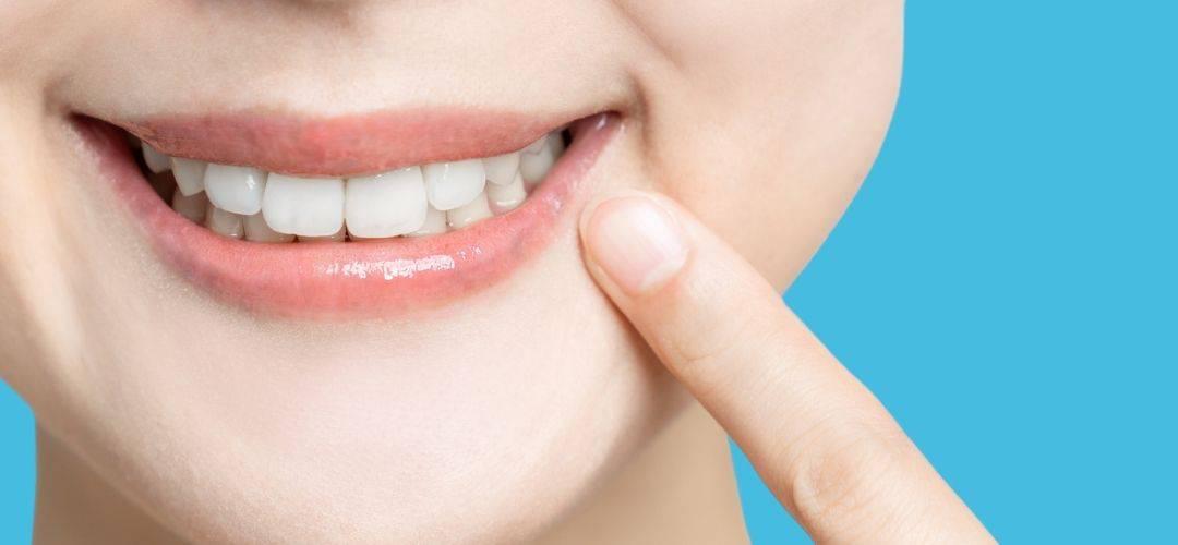 woman pointing at teeth